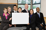 Co-workers posing with blank sign in conference room