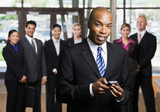 African businessman using cell phone in front of co-workers