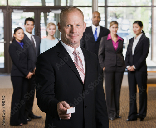 Businessman offering business card in front of co-workers
