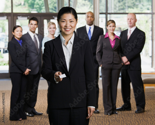Businesswoman offering business card in front of co-workers