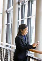 Businesswoman leaning on railing in office and text messaging
