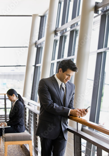 Businesspeople working on laptop and text messaging in lobby