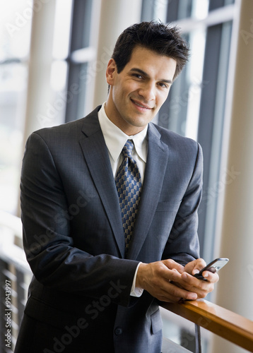 Businessman text messaging on cell phone in office lobby
