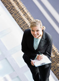 Businesswoman writing on clipboard in office lobby