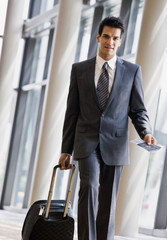 Traveler pulling suitcase, holding passport and airline ticket