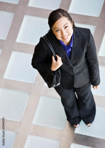 Businesswoman in full suit standing with purse