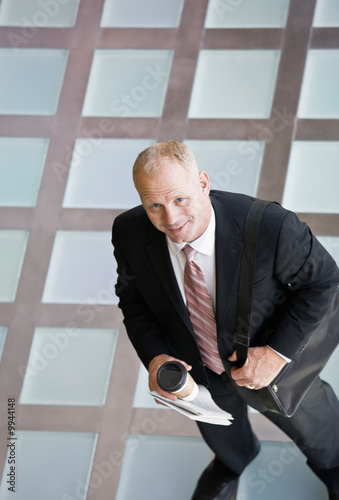 Businessman standing with coffee in the morning