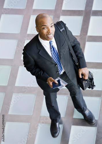 African businessman with briefcase and passport traveling