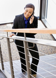 Asian businesswoman talking on cell phone and ascending stairs