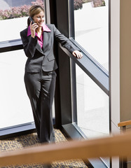 Happy businesswoman talking on cell phone in office building