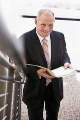 Businessman looking up from paperwork near office stairs
