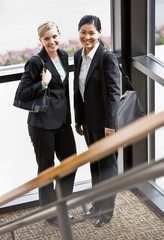 Female co-workers posing together in corner of office building
