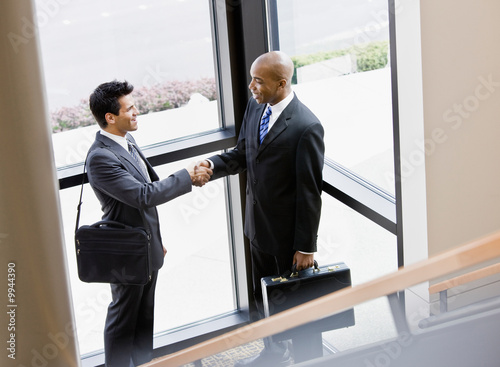 Male co-workers shaking hands in corner of office building
