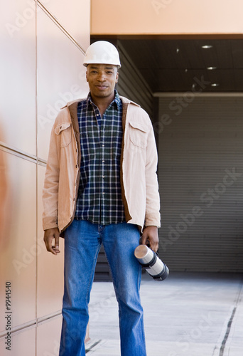 Male construction worker posing in hard-hat with thermos