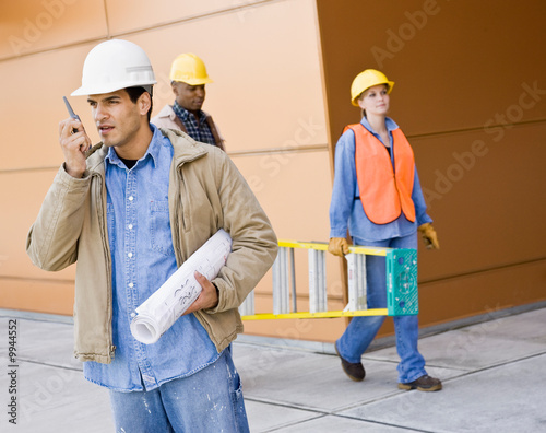 Construction workers carrying ladder, blueprints and talking