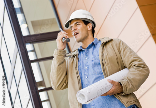Construction worker talking on cell phone and holding blueprints