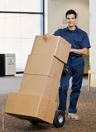 Delivery man pushing stack of cardboard boxes on dolly