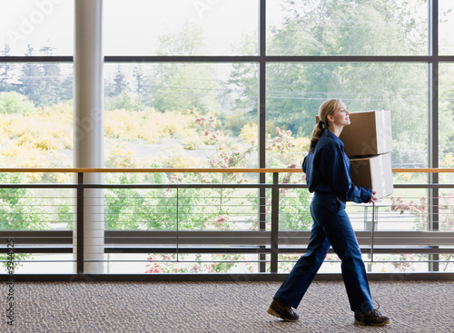 Side view of delivery woman in uniform carrying stack of boxes