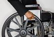 Disabled businessman pushing himself in wheel chair