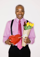 Man holding bouquet of tulips and heart-shaped box