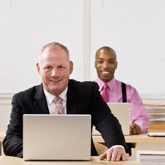 Confident businessman typing on laptop