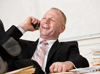 Businessman at desk talking on cell phone with feet up