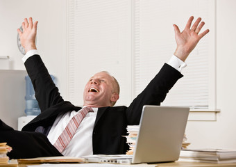Excited businessman cheering with feet up