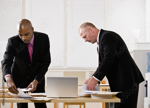 Co-workers searching through paperwork at desk