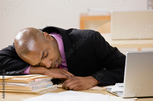 Businessman laying on file folders at desk and sleeping