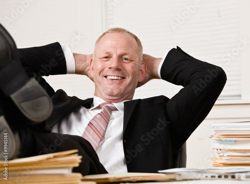 Relaxed businessman at desk with feet up
