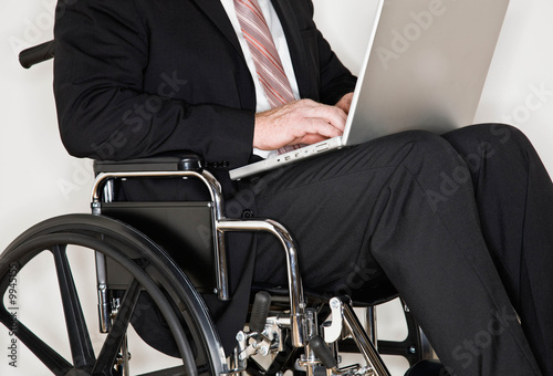 Disabled businessman sitting in wheel chair typing on laptop