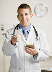 Doctor in lab coat and stethoscope handing prescription from pad