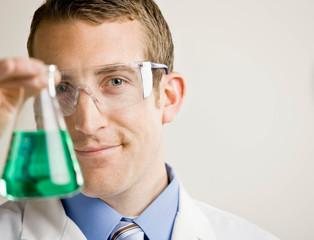 Scientist wearing safety goggles examining beaker of liquid