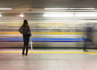 Lone woman watching subway speed by.