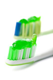 two toothbrushes with green toothpaste isolated poster