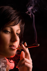 nice young girl is smoking in studio