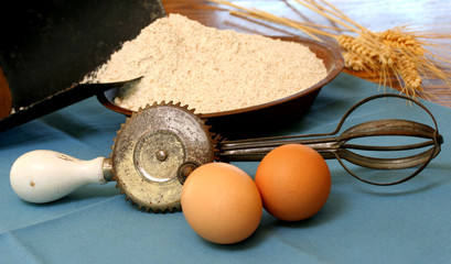 Vintage egg beater, eggs, flour and wheat