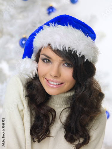 Beautiful woman next to christmas tree on white