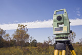 Fall time land surveying - total station set in the field. poster