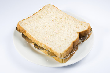 A sandwich filled with coins on a white plate