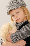 cute blonde girl in checked cap cuddles doll poster