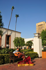 Man playing guitar for money in a train station courtyard