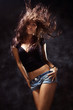 attractive young woman dancing, studio dark background