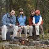 Happy family near campfire poster
