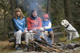 Family with dog near campfire poster
