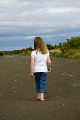 Young child walking alone down empty road