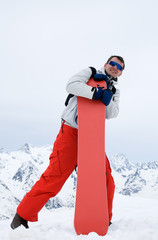 Smiling man with snowboard in red pants