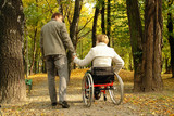Husband and handicapped wife taking stroll in park alley poster