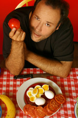 man holding a tomato while sitting at a table