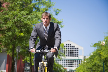 A caucasian businessman riding a bicycle to work